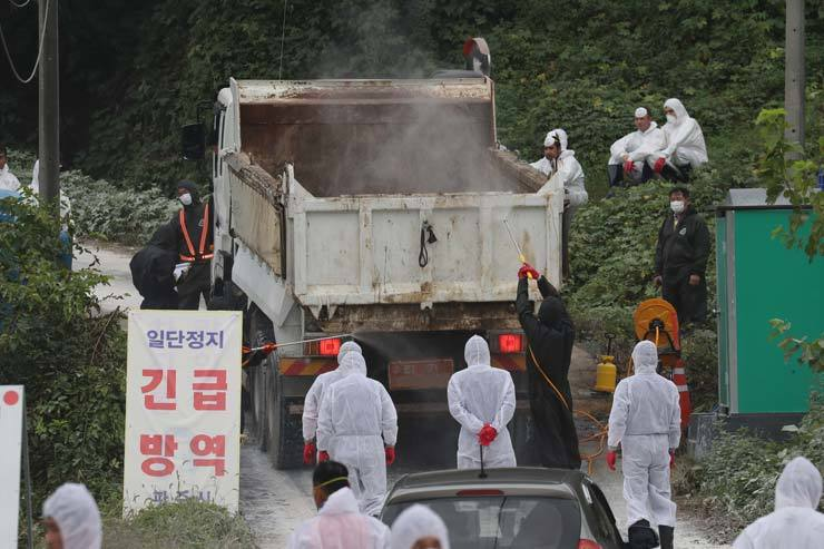 Workers fumigate vehicles entering Papyeong in Paju, Gyeonggi Province, where an additional African swine fever case was confirmed at a farm there, Wednesday. / Yonhap