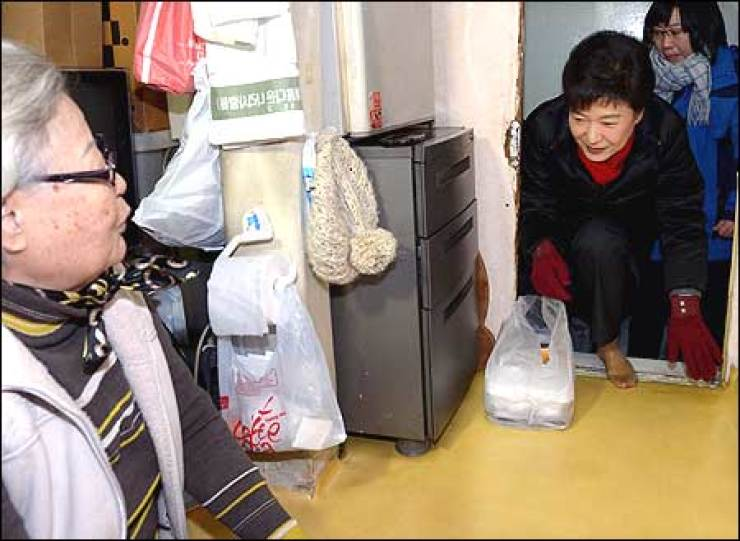 President-elect Park Geun-hye enters a small one-room household to deliver a lunchbox to an elderly woman in the underprivileged district of Changsin-dong, Seoul, on Christmas Day, Tuesday. Yonhap