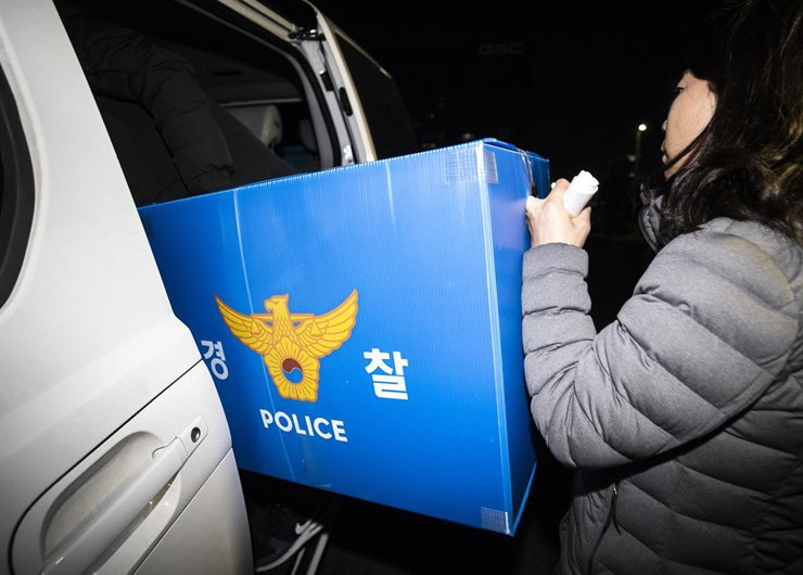 A police officer loads seized articles into a vehicle after the search and seizure of Burning Sun nightclub in southern Seoul on Feb. 14. / Yonhap