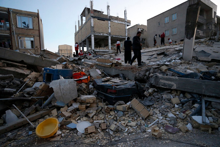 In this photo provided by the Iranian Students News Agency, ISNA, people look at destroyed buildings after an earthquake at the city of Sarpol-e-Zahab in western Iran, Monday. / AFP-Yonhap