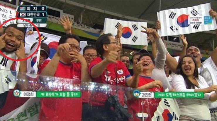 A spectator in circle makes 'slanted eyes' while cheering for South Korea at the Fonte Nova Arena in Salvador on Aug 5. / Courtesy of MBC