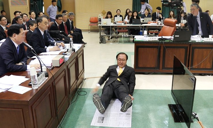 Rep. Roh Hoe-chan of the minor opposition Justice Party lies on newspapers to demonstrate the average floor space given to a prison inmate, 1.06 square meters, during a parliamentary inspection into the Board of Audit and Inspection in Seoul, Thursday. Former President Park Geun-hye, who has been jailed while on trial over a corruption scandal, claimed her human rights have been violated at the detention center, although the cell she occupies by herself is 10.08 square meters in area. / Yonhap