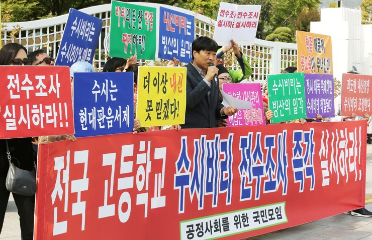 A civic group calls on the government to investigate possible school record manipulation and exam leaks at all high schools across the nation in a rally in front of the Government Complex in Seoul, Tuesday. / Yonhap