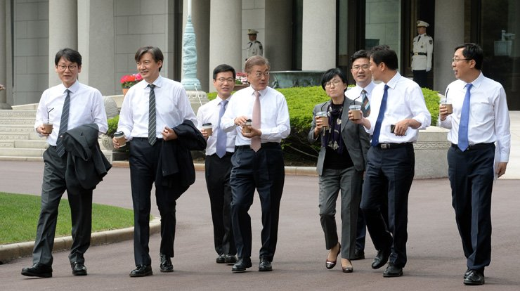 President Moon Jae-in strolls with newly appointed secretaries at Cheong Wa Dae, Thursday. They are, from left, Kwun Hyuk-ki, head of the press center at Cheong Wa Dae; Cho Kuk, senior secretary for civil affairs; Lee Joung-do, secretary for administrative affairs; Moon; Cho Hyun-ock, senior secretary for personnel affairs; Song In-bae, a Democratic Party of Korea official; Im Jong-seok, chief of staff; and Yoon Young-chan, senior secretary for public affairs. / Joint Press Corps