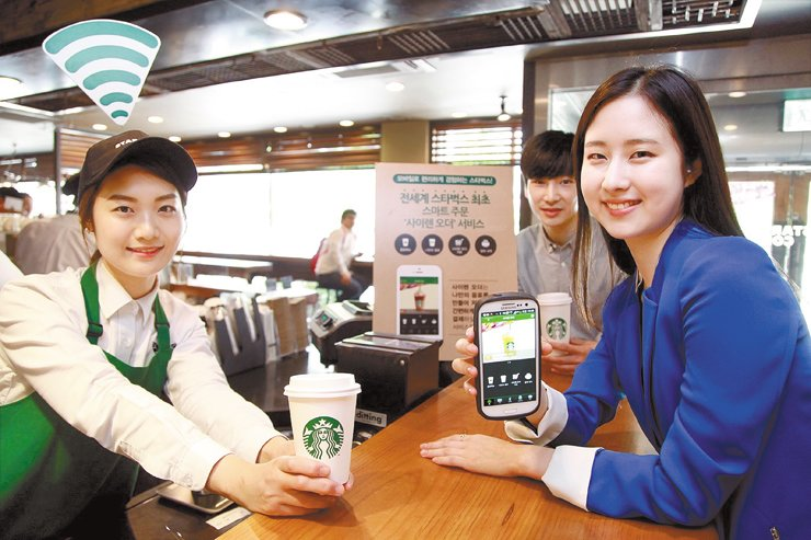 Starbucks Coffee Korea employees pose with a smartphone and a cup of latte at a Starbucks Coffee shop in Seoul as its customers made more than 20 million orders via its Siren Order application. The coffee chain said it will offer free coffees to 16,000 customers from May 2 to 8. / Courtesy of Starbucks Coffee Korea
