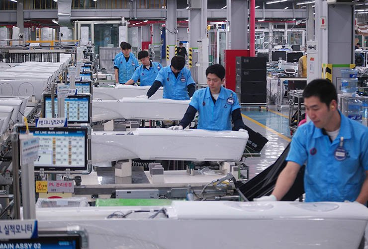 Samsung Electronics employees assemble parts for an air conditioner at the company's manufacturing line in Gwangju, Tuesday. The company has replaced the conveyor belt manufacturing system with the modular production method in which a veteran worker takes charge of a product from assembly to performance check. / Courtesy of Samsung Electronics