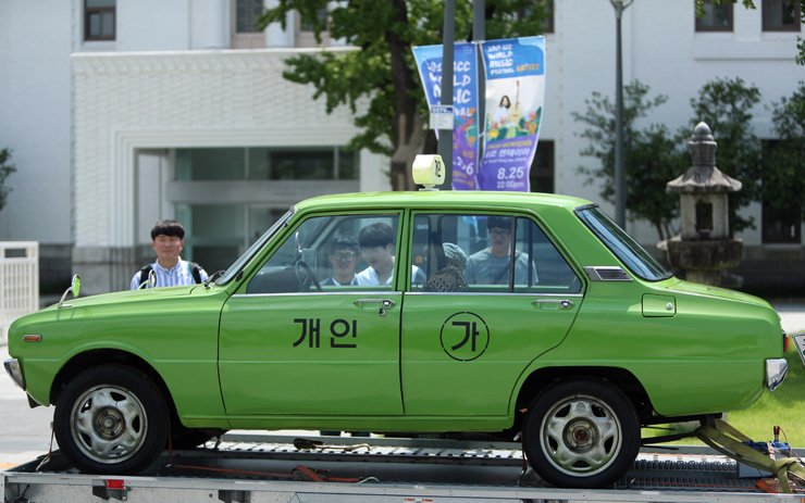 The taxi that appeared in the mega-hit movie 'A Taxi Driver' is exhibited in front of former South Jeolla Provincial Office in Gwangju, South Jeolla Province, to celebrate the movie's attracting over 10 million audiences, Sunday. / Yonhap