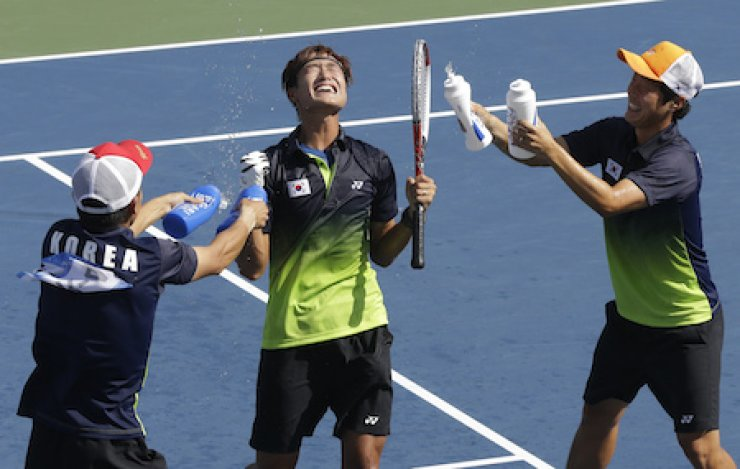 South Korean soft tennis player Kim Hyeong-jun, center, celebrates with teammates after defeating Japan's Koichi Nagae to win the gold medal during the men's team soft tennis final match at the Incheon Asian Games, Saturday. /AP-Yonhap