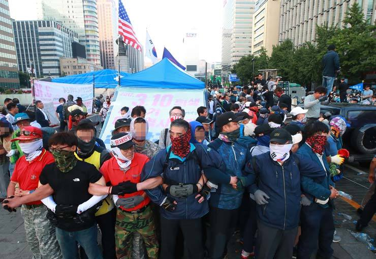 Members and supporters of the Our Republican Party form scrummage to resist Seoul City's effort to remove tents set up at Gwanghwamun Square in centrall Seoul, Monday. / Yonhap