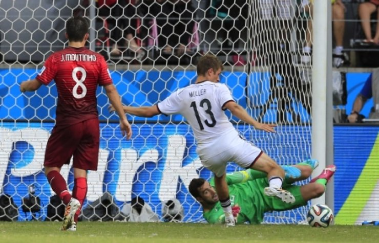 Germany's Thomas Muller, center, scores his side's third goal during the Group G World Cup  match aganist Portugal at the Arena Fonte Nova in Salvador, Brazil. /AP-Yonhap