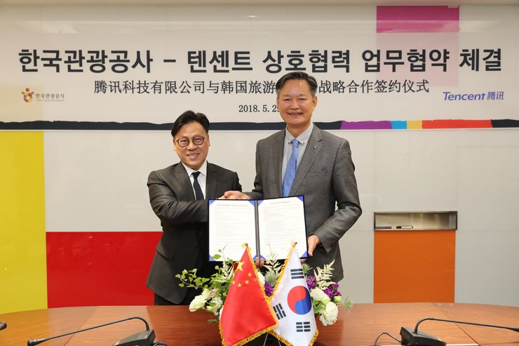 Min Min-hong, right, executive vice president for international tourism at the Korea Tourism Organization (KTO), shakes hands with Steven Chang, Tecent's corporate vice president, at the KTO's Seoul office, Tuesday, after signing a business agreement to increase Chinese visitors to Korea. / Courtesy of Korea Tourism Organization