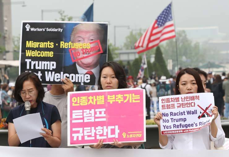 A progressive group holds a rally at Gwanghwamun Square in central Seoul, Friday, to denounce U.S. President Donald Trump's racist and anti-immigrant policies ahead of his planned visit to Korea over the weekend; while a conservative group behind them holds its own gathering welcoming the visit. / Yonhap