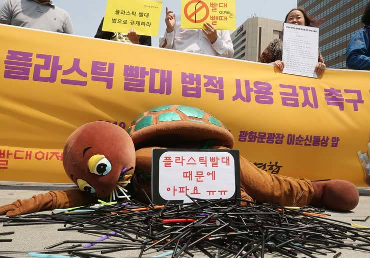 An activist clad in a turtle costume urges the government to ban use of plastic straws at restaurants and coffee shops, during a press conference at Gwanghwamun Square in central Seoul, Tuesday. / Yonhap