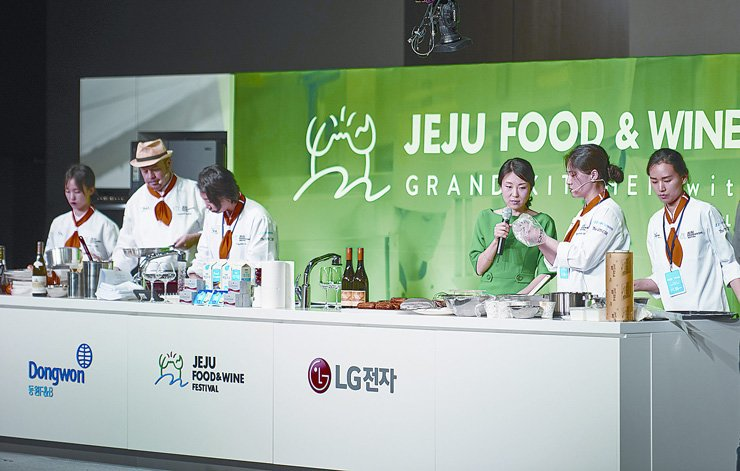 Chef Laurent Dallet, second from left, patissier Lee Hyun-hee, second from right, and their culinary teams demonstrate how to cook the creative dishes they prepared for the JFWF during the Grand Kitchen with Masters, a program for students, at Halla University on Jeju Island, May 18.  / Courtesy of JFWF