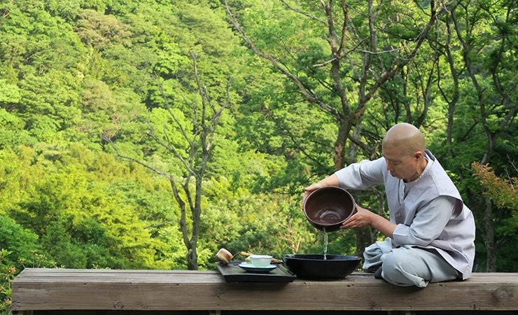 Buddhist nun Jeong Kwan pours water into a bowl to prepare lotus flower tea outside the Chunjinam Hermitage of the Baekyangsa Temple in Jangseong County, South Jeolla Province, May 29.  Korea Times photo by Yun Suh-young