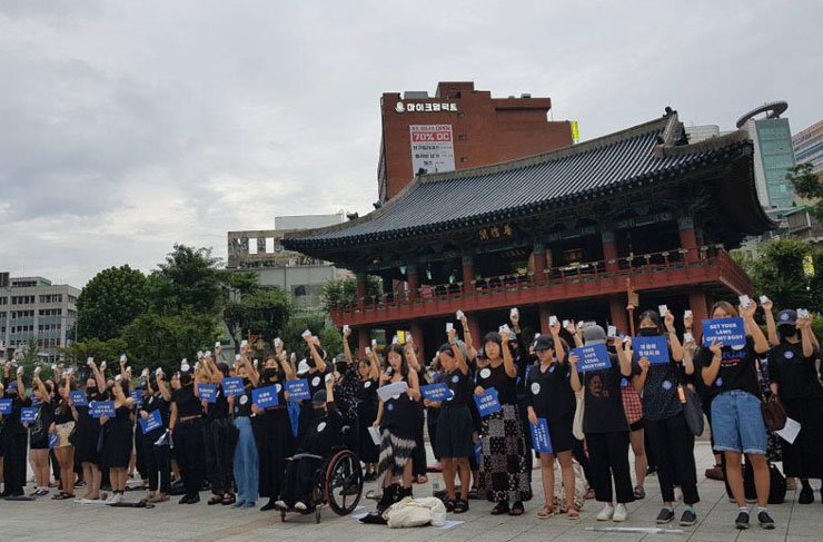 Women hold up abortion pill boxes in front of Bosingak, a pavillion at Jongno, downtown Seoul on Aug. 26. 125 women - roughly the number of women who get an abortion every hour in South Korea - gathered to give a Mifegyne-swallowing performance using vitamin pills. / Yonhap