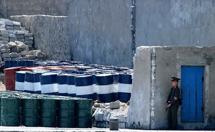 In this May 8, 2016, file photo, a North Korean solder stands guard near barrels stacked up near the river bank of the North Korean town of Sinuiju, opposite the Chinese border city of Dandong. / AP-Yonhap