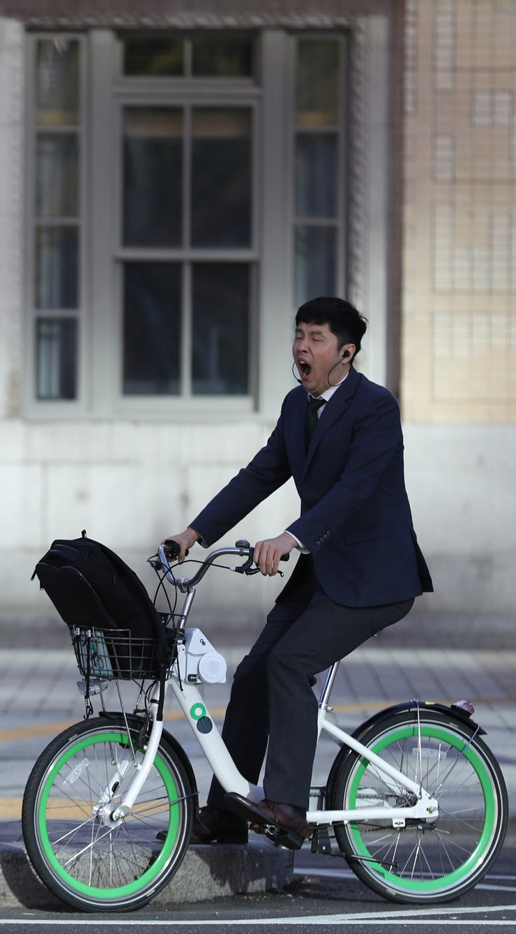 A cyclist yawns while riding his Ttareungyi bike to work after the Chuseok holidays, Thursday. / Yonhap