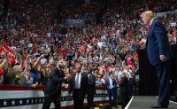 Trump denounces Dems at rally, plays down race