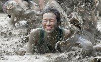 Revellers jump into sludge at Korea's annual mud festival