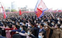 North Koreans rally wearing masks after military parade