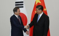 Moon set for China trip to meet Xi, Abe and join trilateral summit