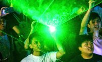 Protesters shine laser beams on arrest of Hong Kong student