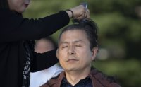 Opposition leader has his head shaved; declares all-out fight against Moon