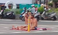 Foreign men sunbathing on road baffle Taiwan motorists