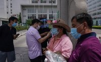 Beijing battles 'explosive coronavirus outbreak' as food market cases mount