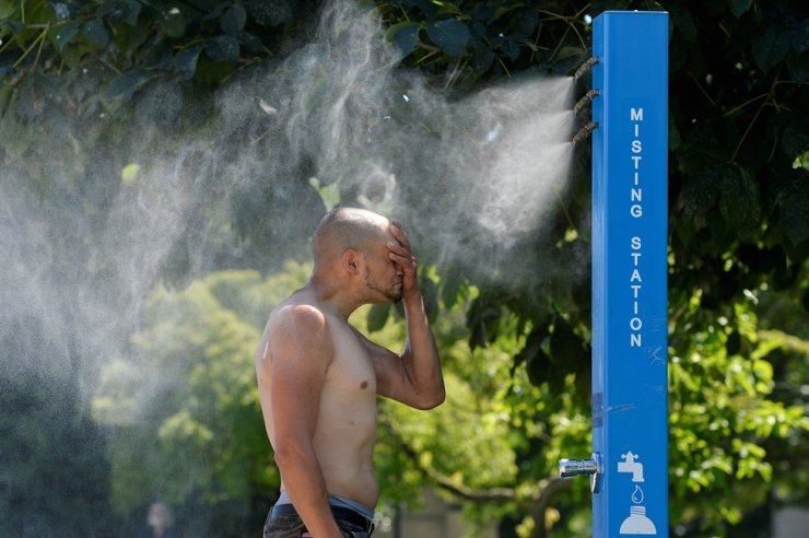 A man cools off at a misting station during the scorching weather of a heat wave in Vancouver, British Columbia, Canada, June 27. Reuters-Yonhap