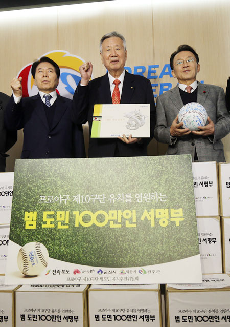 KT Chairman Lee Suk-chae, second from left, and Suwon Mayor Yeom Tae-young, left, pose before submitting an application at the headquarters of the Korea Baseball Organization Monday to create a 10th club in the Korean league.                                                                                                                           / Yonhap