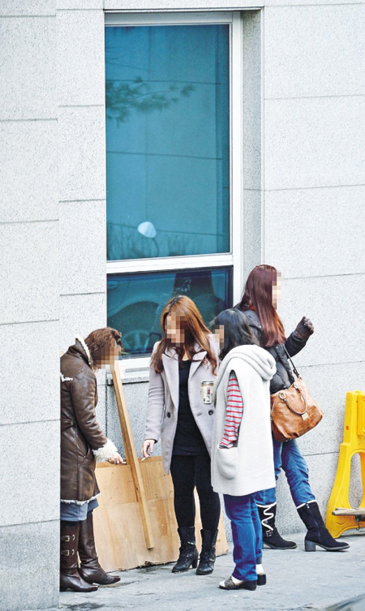 A group of women smoke outside an office building in Chungmuro, Jung-gu, Seoul, Tuesday. Female smokers say that prejudice against women smokers is still prevalent in Korean society. / Korea Times photo by Shim Hyun-chul