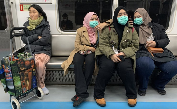 People wear masks to prevent catchign the coronavirus (COVID-19)  in Seoul, South Korea, Tuesday, Feb. 25, 2020. South Korea and China each reported hundreds more virus cases Thursday as the new illness persists in the worst-hit areas and spreads beyond borders. Korea Times photo by Choi Won-suk