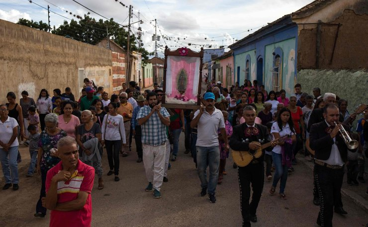 People take part in a religious procession during the Virgin of Guadalupe day in Bobare, Lara state, Venezuela, on December 12, 2019. - Faced with the economic crisis and the mega-inflation that affects the country, Venezuelans opt for low-cost alcoholic beverages produced locally. AFP