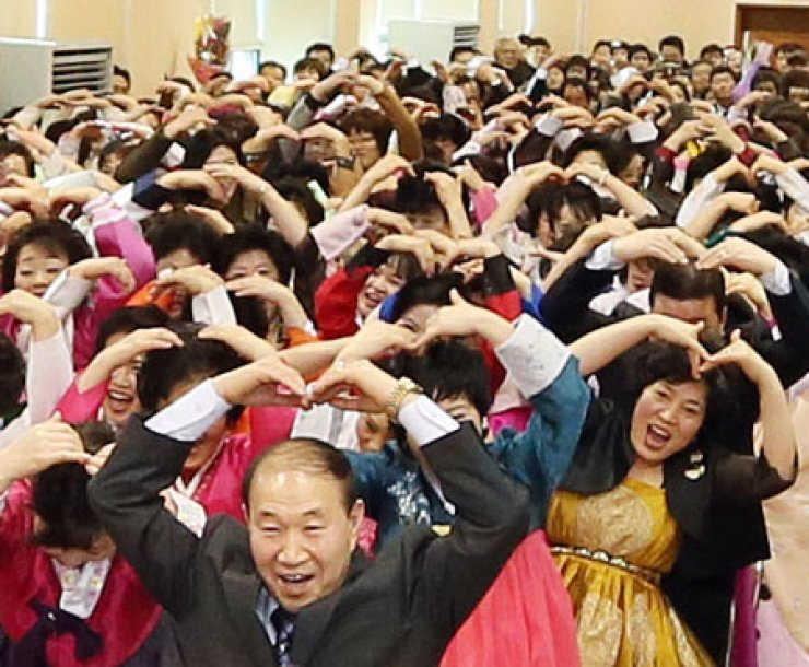 Graduates with an average age in the mid-50s form the shape of a heart with their hands to express thanks to their teachers at a graduation ceremony at Nam Incheon Middle and High School in Incheon, Thursday. The school provides a program for those who are over 20 and missed the opportunities to complete their middle and high school studies.       / Yonhap