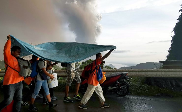 People take cover under a large plastic sheet as a column of ash spews from erupting Taal Volcano over Tagaytay city, Philippines, 12 January 2020. According to media reports, evacuations are underway as the volcano spewed ash as high as 1,000 meters into the sky. EPA