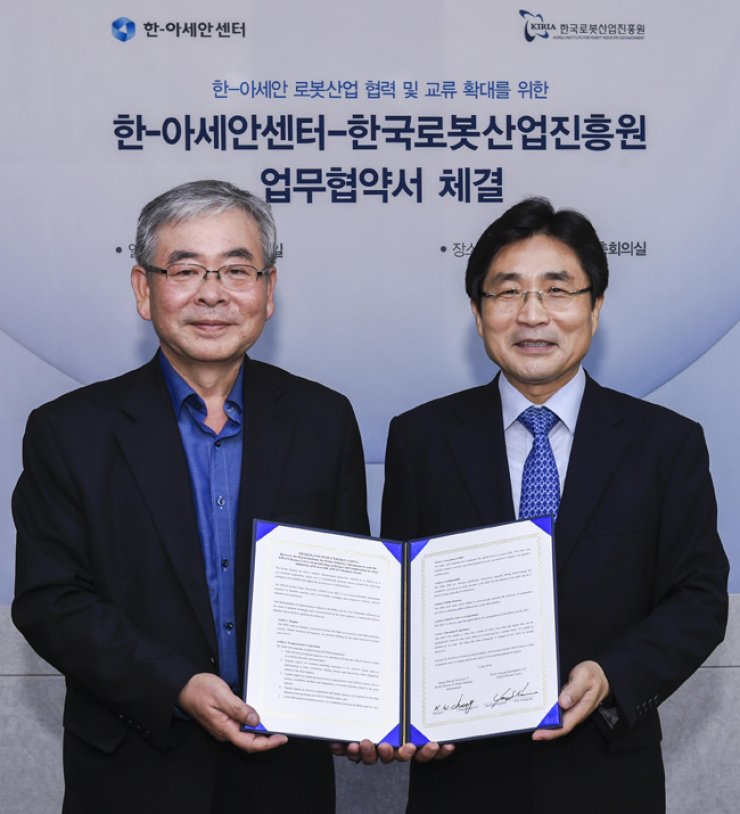 ASEAN-Korea Centre Secretary General Kim Young-sun, right, poses with Korea Institute for Robot Industry Advancement President Jung Kyung-won at the ASEAN-Korea Centre in Seoul on July 12./ Courtesy of the ASEAN-Korea Centre