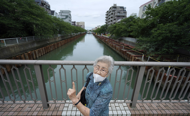 Kisako Motoki, 86, speaks, looking though a red cellophane depicting what she saw the atmosphere of the night of the Great Tokyo Air Raid on March 10, 1945, during an interview with the Associated Press at the Center for the Tokyo Raids and War Damage in Tokyo Wednesday, July 29, 2020.  In Japan, war orphans were punished for surviving. They were bullied. They were called trash, sometimes rounded up by police and put in cages. Some were sent to institutions or sold for labor. They were targets of abuse and discrimination. Now, 75 years after the war's end, some are revealing their untold stories of recovery and pain, underscoring Japan's failure to help its own people. AP
