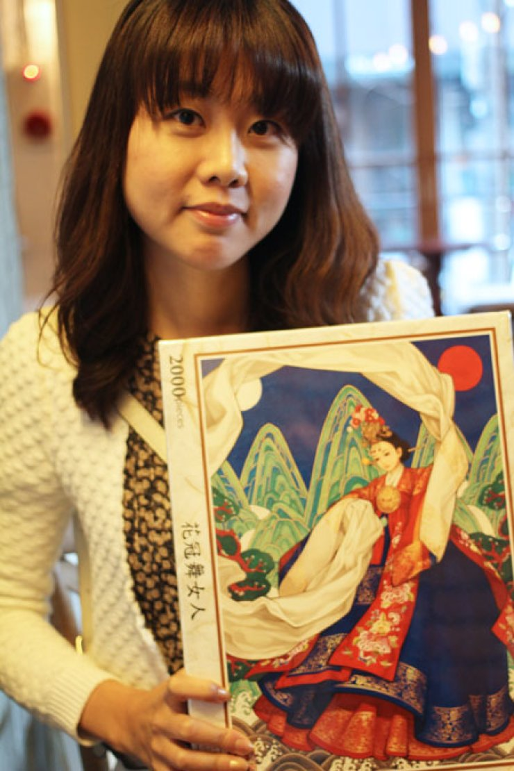 Illustrator Wooh Na-young poses with one of her drawings. / Korea Times
