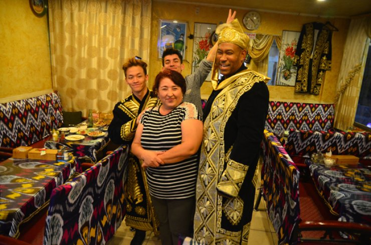 Foreign customers try on Uzbek chapan robes and pose with a worker at Samarkand Restaurant in Gwanghui-dong. This weekend, the area will be flooded with migrant workers looking for a hot meal and good times.  /  Coutesy of Jon Dunbar