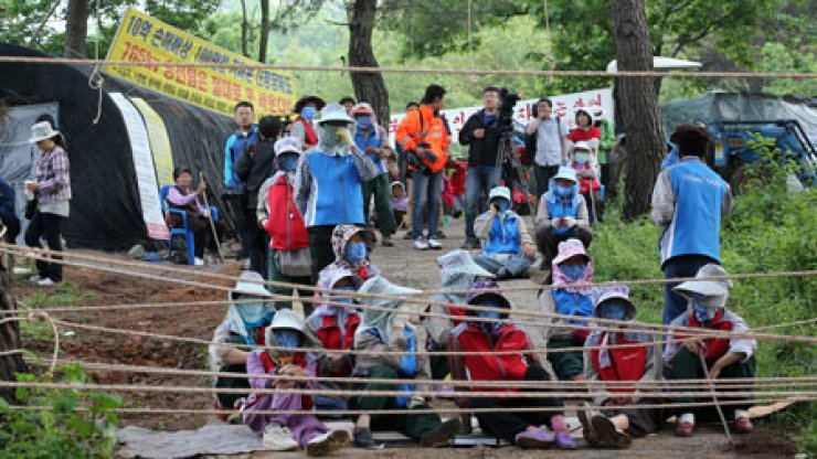 Residents of Miryang, South Gyeongsang Province, rally behind a barricade set up near the mouth of Pyeongbat Village, Monday, to prevent Korea Electricity Power Corp. workers from resuming building transmission towers there. / Yonhap