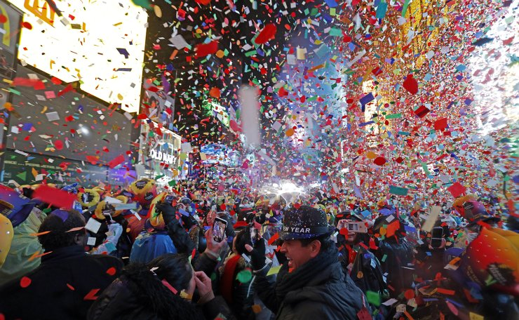 In this Tuesday, Jan. 1, 2019, file photo, Joey Flores, of California, uses his cellphone as confetti falls during a New Year's celebration in New York's Times Square. New York City's counterterrorism czar expects Times Square to be
