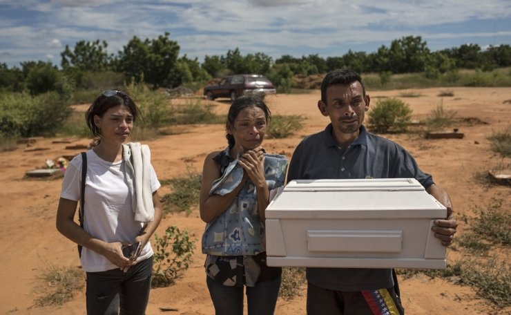Roberto Parra carries the remains of his son Matias Alejandro alongside his wife Maria Isabel Parra and daughter Alejandra Parra at San Sebastian municipality cemetery before burying him in Maracaibo, Venezuela, Nov. 27, 2019. Parra said his 19-day-old boy died after he was born with lung problems at a public hospital, where, after his wife was turned away from the first hospital, was left to deliver alone in a dirty chair before doctors rushed her up the stairs with her baby's head already exposed. Although the baby was born with respiratory problems, they were told to take him home because he could get sicker if they stayed. AP