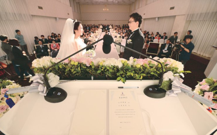 A bride and groom exchange a wedding vow during the ceremony held without an officiator. Some young couples have their fathers preside over the ceremony for a simpler wedding. / Korea Times file