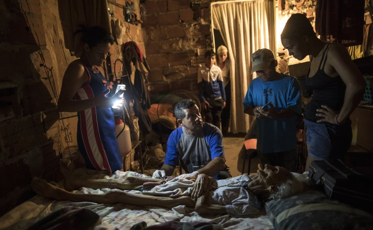 Community activist Carolina Leal uses a cell phone to light up the work area for Roberto Molero as he prepares the body of Teresa Jimenez, 91, after she died of natural causes in her home in Maracaibo, Venezuela, Nov. 17, 2019. Molero embalms bodies with no training other than seeing it done during a decade that he work as a driver at a funeral home, while Leal assumes the role of funeral director in her poor and often violent Maracaibo neighborhood, hoping to rid families of unnecessary misery she's seen too many times. AP