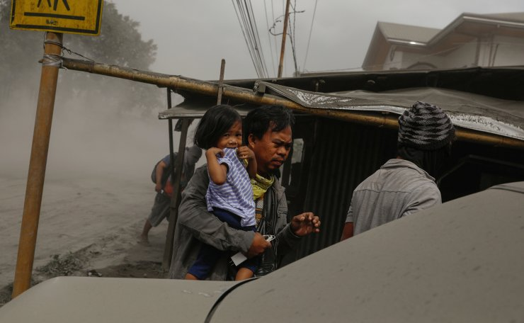 A family living near the errupting Taal Volcano evacuates in Lemery, Batangas City, Philippines, January 13, 2020. Reuters