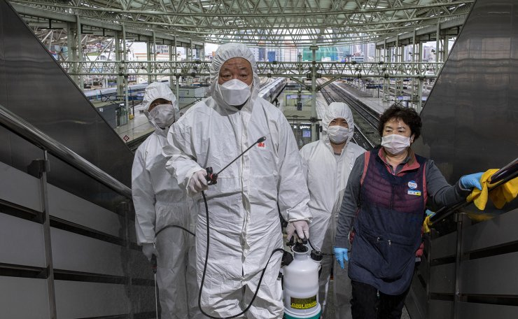 Workers wearing protective gears spray disinfectant as a precaution against the coronavirus at a train station t in Seoul, South Korea, Tuesday, Feb. 25, 2020. Korea Times photo by Shim Hyun-chul