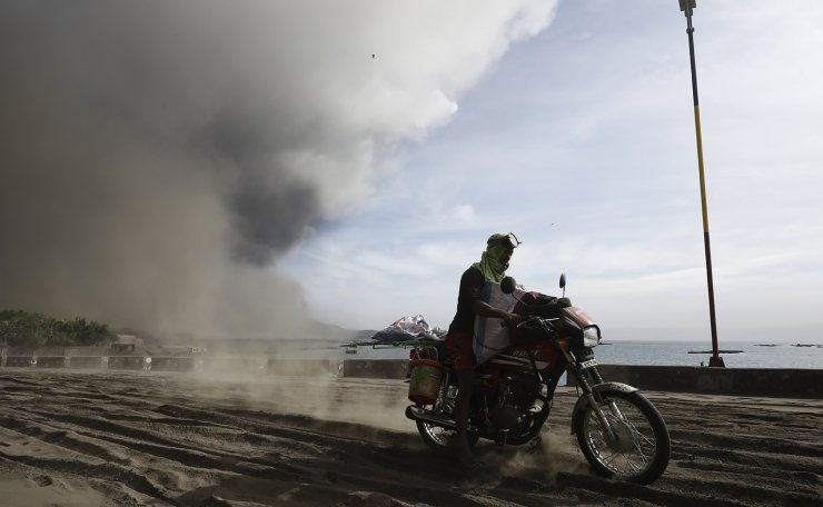 A person rides a motobike on a road covered in ash deposits, a day after the eruption of Taal Volcano, in Agoncillo town in Batangas province, Philippines, 13 January 2020. Thousands of people have been ordered to evacuate as authorities in the Philippines raised the alert status, due to the increased activity, of the Taal Volcano, located near Manila. The Philippine Institute of Volcanology and Seismology (PHIVOLCS) raised the alert level from one to three, before raising it to four. EPA
