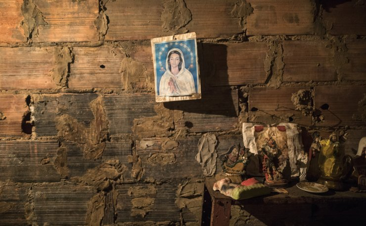 An image of the Virgin Mary hangs from a brick wall next to the room where the corpse of Teresa Jimenez is prepared following her death from natural causes at the age of 91 in Maracaibo, Venezuela, Nov. 17, 2019. The cost of transporting a body, buying a casket and burial plot for a funeral can run into the hundreds of dollars, or more, while most earn the minimum wage of roughly $3 a month as hyperinflation devours pay.  AP